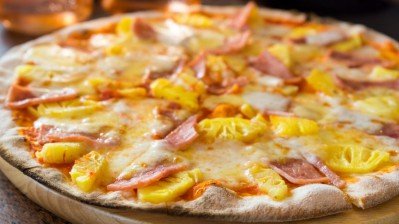 ham and pineapple pizza on wooden table with Spoon and Fork Tied, food concept